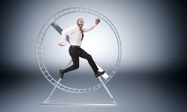 Happy to work hard. Caucasian businessman in hamster wheele is happy to work hard royalty free stock photos