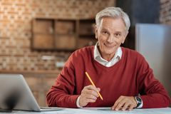 Cheerful senior engineer posing while drawing blueprint. Happy to work. Upbeat senior engineer sitting at the table, holding a pencil and a protractor and Stock Images