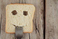 Happy toast with a fork in her mouth on a board Stock Photo