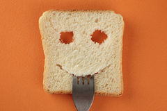 Happy toast with a fork in her mouth. On a cutting board Stock Photos