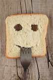 Happy toast with a fork in her mouth on a wooden Royalty Free Stock Photography