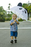 Happy toddler. Toddler holding his umbrella on a rainy day Stock Photos