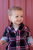 Happy Toddler. Happy young toddler boy in plaid button down shirt, smiling with red background Stock Images
