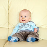 Happy toddler. Sitting on sofa and smiling royalty free stock photography