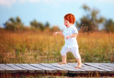 Happy toddler baby running the path on summer field Stock Images