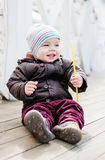 Happy toddler baby boy sitting by the fence Royalty Free Stock Images