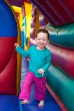 Happy toddler bounce in trampoline. Happy laughing redhead toddler bounce in a colorful trampoline Royalty Free Stock Photos