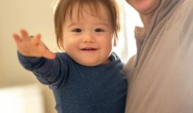 Happy toddler boy being held by his parents royalty free stock photo