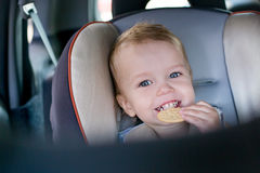 Happy toddler boy in car. Happy Toddler boy in the car eating cookies Stock Images