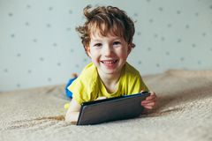 Happy toddler boy having fun playing game on gadget ,Preschool kid sititng on sofa with smiling face watching cartoon on smart pho stock photos