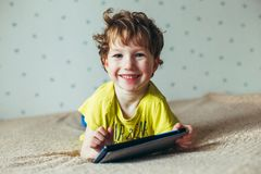 Happy toddler boy having fun playing game on gadget ,Preschool kid sititng on sofa with smiling face watching cartoon on smart pho royalty free stock photography