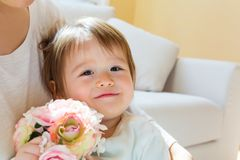 Toddler boy with his mother holding flowers Stock Photo