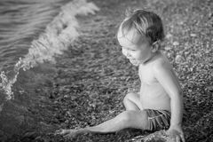 Happy toddler boy playing on the sea Stock Photos