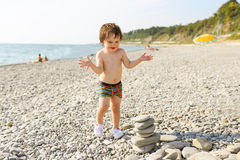 Happy toddler building pebbles tower on the beach Royalty Free Stock Photo