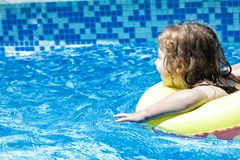 Happy toddler child in a family swimming pool. Happy toddler child with swimming ring in a family pool with negative space Royalty Free Stock Photography