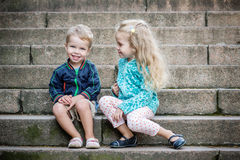 Happy toddler children sit on the steps Stock Photo