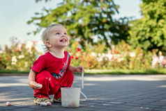 Happy toddler draws with chalk. On asphalt Stock Images