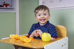 Happy toddler eating fruit Stock Images
