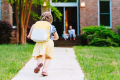 Happy Toddler girl arriving home from school. With a backpack stock photos