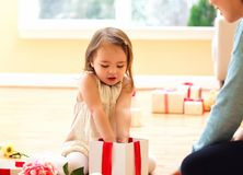 Happy toddler girl with a Christmas present. Box Stock Images
