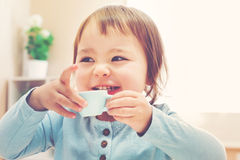 Happy toddler girl drinking from a teacup Stock Images