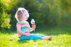 Happy toddler girl eating ice cream in a garden Royalty Free Stock Image