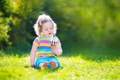 Happy toddler girl eating ice cream in a garden Stock Photo