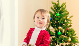 Happy toddler girl in front of her Christmas tree Royalty Free Stock Image