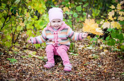 Happy toddler girl gathers leaves Royalty Free Stock Photos