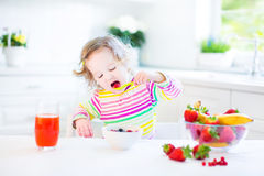 Happy toddler girl having breakfast drinking juice Royalty Free Stock Images