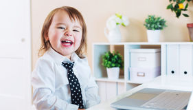 Happy toddler girl laughing while using a laptop Stock Photos