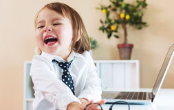Happy toddler girl laughing while using a laptop Royalty Free Stock Photo