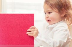 Happy toddler girl opening big red binder Stock Photos