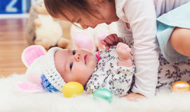 Happy toddler girl playing with her baby sister on Easter Royalty Free Stock Photo
