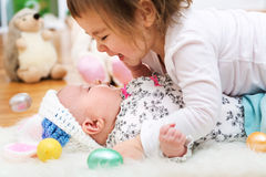 Happy toddler girl playing with her baby sister on Easter Stock Image