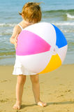 Happy toddler girl playing with her colorful ball at beach Royalty Free Stock Photo