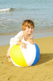 Happy toddler girl playing with her colorful ball at beach Royalty Free Stock Image