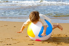 Happy toddler girl playing with her colorful ball at beach Stock Images