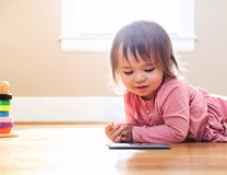 Happy toddler girl playing with her tablet computer Stock Photos