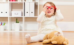 Happy toddler girl playing with her teddy bear and glasses Stock Image