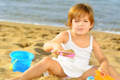 Happy toddler girl playing with her toys at beach Stock Photography