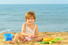 Happy toddler girl playing with her toys at beach Royalty Free Stock Images