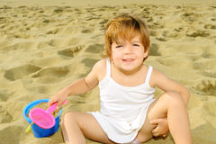 Happy toddler girl playing with her toys at beach Royalty Free Stock Photos