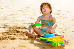 Happy toddler girl playing with her toys at beach Stock Photo