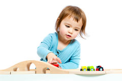 Happy toddler girl playing with trains Stock Images