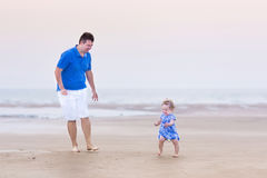 Happy toddler girl runnig at beach with her father Stock Photography