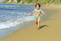Happy toddler girl running at beach Stock Photo