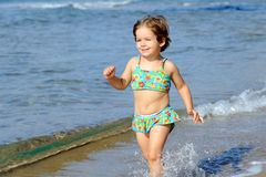 Happy toddler girl running at beach Royalty Free Stock Photos