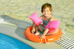 Happy toddler girl siting next to swimming pool Royalty Free Stock Photo