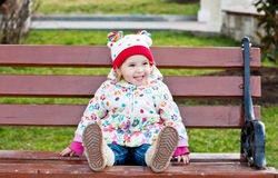 Happy toddler girl sitting on the bench Stock Photos